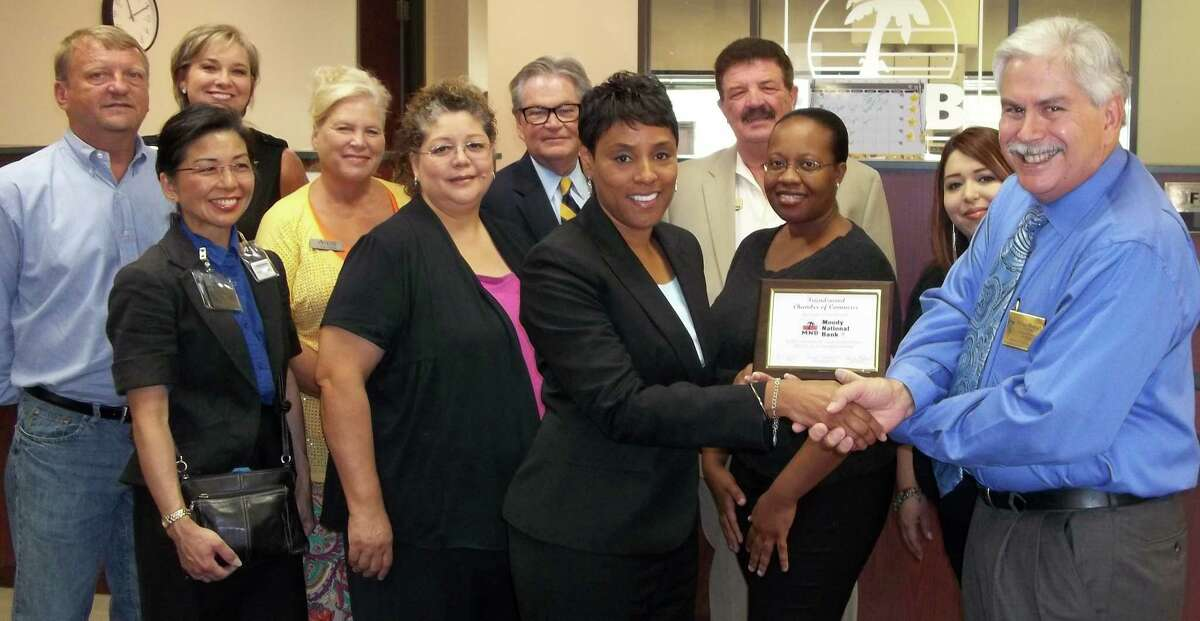 Sharon Brown, branch manager of Moody National Bank in Pearland, accepts a plaque naming the bank the Friendswood Chamber of Commerce Business of the Month for August, from chamber chairman Robert Rinehart. Pictured with Brown and Rinehart are chamber ambassador team members and staff along with bank staff.