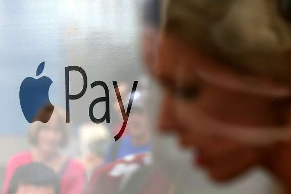 The Apple Pay logo is displayed in a mobile kiosk sponsored by Visa and Wells Fargo to demonstrate the new Apple Pay mobile payment system on October 20, 2014 in San Francisco City. Apple's Apple Pay mobile payment system launched today at select banks and retail outlets. (Photo by Justin Sullivan/Getty Images)
