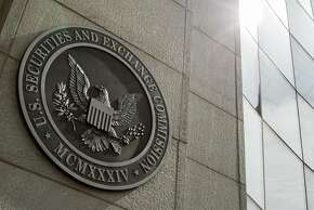 FILE - This June 19, 2015 file photo shows the seal of the U.S. Securities and Exchange Commission at SEC headquarters, in Washington. The Securities and Exchange Commission on Wednesday, Aug. 5, 2015 voted to order most public companies to disclose the ratio between their chief executives' annual compensation and median, or midpoint, employee pay. The new rule will take effect starting in 2017. (AP Photo/Andrew Harnik, File)