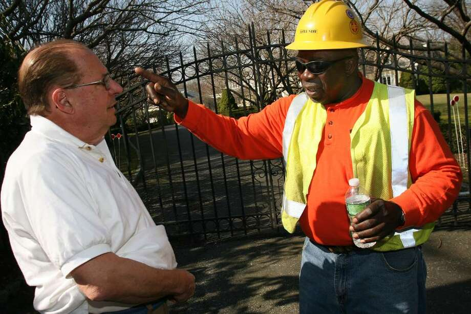 George Thomas of the Asplundh Power Line Division out of Allentown, Pennsylvania speaks with Greenwich homeowner Jerry Davis about the power outage in Mr. Davis's  neighborhood caused by last weekends storm. Photo: David Ames, David Ames/For Greenwich Time / Greenwich Time