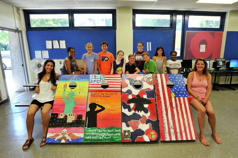 Pathfinders Adventure Camp Art Director Kellie Austin, left, and counselor for children with special needs Georgia Monahan, at right,with some of the campers who helped decorate four cornhole boards for the Darien VFW chapter at Cloonan Middle School in Stamford on Friday. Twenty-one kids from Pathfinders Adventure Camp, based at the middle school, decorated the four cornhole boards that will go to the Darien chapter of the Veterans of Foreign Wars. Campers are, from left, Emma Thompson, Jaimie Ammon, Anton Ammon, Caitlin Reynolds, Owen Pollard, Riley Morris, Zac Kitay, Julia Hatzis and Sherley Renodo. Photo: Jason Rearick / Hearst Connecticut Media / Stamford Advocate