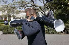 A White House aide carries prosthetic limbs for veterans while they participate in the Wounded Warrior Project's Soldier Ride, hosted by President Barack Obama, Thursday, April 17, 2014, at the White House in Washington. The cyclists were in specially built bikes that could accommodate amputations or other injuries. (AP Photo/J. Scott Applewhite)