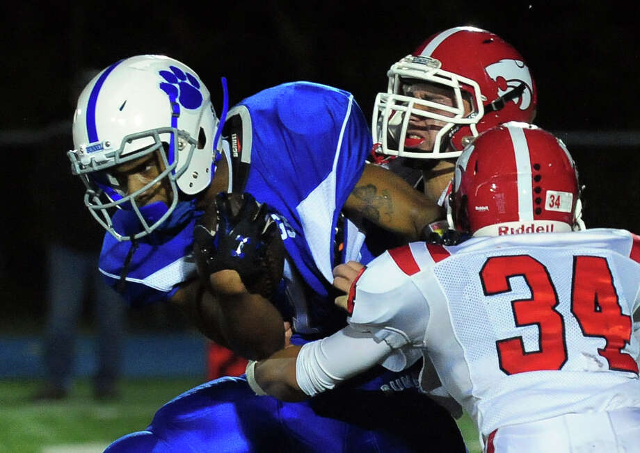 Bunnell's Zhyaire Fernandes tries to break through two Masuk linemen, during football action in Stratford, Conn., on Friday Sept. 26, 2014. Photo: Christian Abraham / Christian Abraham / Connecticut Post