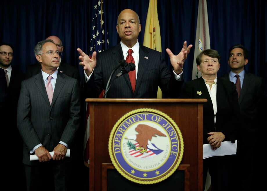 Secretary of Homeland Security Jeh Johnson (center) speaks during Tuesday's news conference in Newark, N.J. An international group of hackers and stock traders made $30 million by breaking into the computers of newswire services that put out corporate news releases and trading on the information before it was made public, federal prosecutors said Tuesday. Photo: Seth Wenig /Associated Press / AP