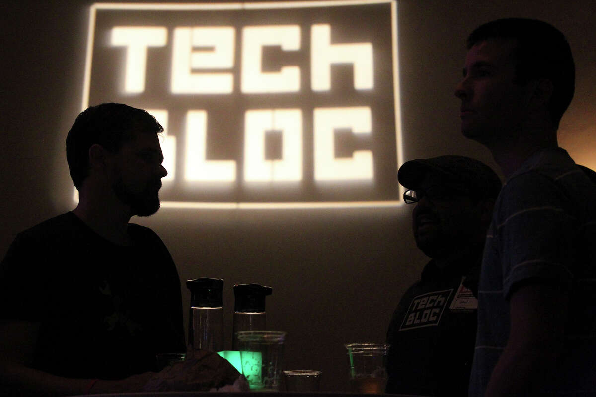 Attendees visit Tuesday while waiting for the speakers at the Tech Bloc event at the Pearl Stables.