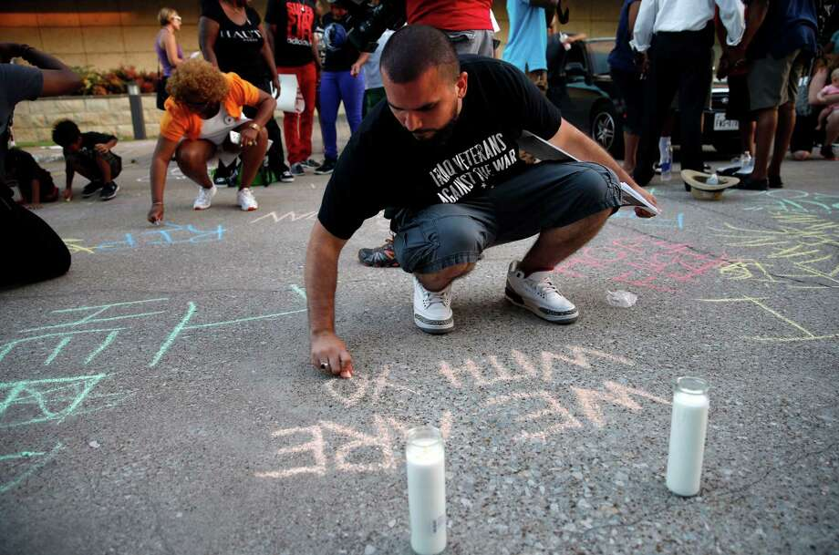 Ramon Mejia writes with chalk on the pavement outside the Arlington Police Department during a vigil for Christian Taylor, Monday, Aug. 10, 2015, in Arlington, Texas. Taylor was killed by police at a car dealership on Friday, Aug. 7. (G.J. McCarthy/The Dallas Morning News via AP) MANDATORY CREDIT; MAGS OUT; TV OUT; INTERNET USE BY AP MEMBERS ONLY; NO SALES Photo: G.J. McCarthy, MBR / Associated Press / The Dallas Morning News
