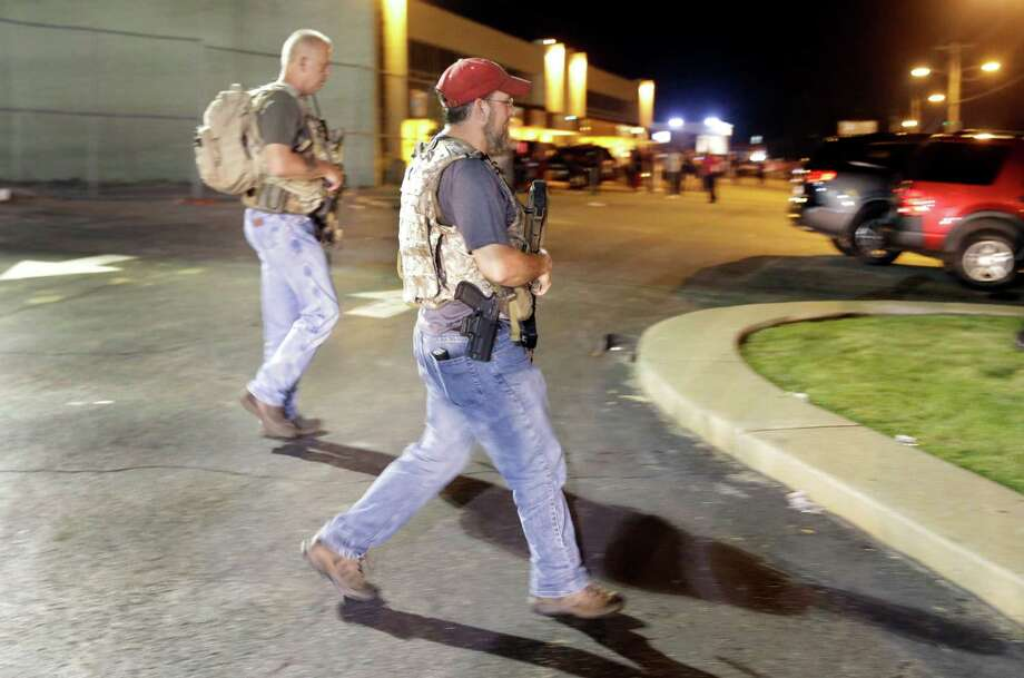 """Heavily armed civilians with a group known as the Oath Keepers arrive in Ferguson, Mo., early Tuesday, Aug. 11, 2015. The far-right anti-government activists, largely consists of past and present members of the military, first responders and police officers. St. Louis County Police Chief Jon Belmar said the overnight presence of the militia group, wearing camouflage bulletproof vests and openly carrying rifles and pistols on West Florissant Avenue, the hub of marches and protests for the past several days, was """"both unnecessary and inflammatory."""" (AP Photo/Jeff Roberson) Photo: Jeff Roberson, STF / Associated Press / AP"""