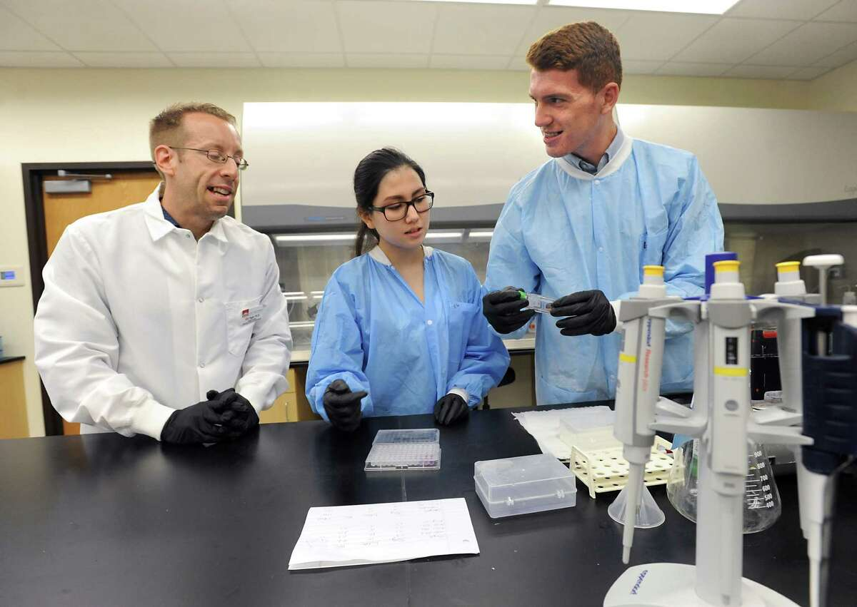 Eric Yager, assistant professor at Albany College of Pharmacy and Health Sciences, left, helps Albany High School students Emily Ha, 16, and Dhimiter Cobani, 17, study protein produced by flu infected cells at the Albany College of Pharmacy and Health Sciences on Tuesday, Aug. 11, 2015 in Albany, N.Y. The students have been involved in a summer research project at the school. (Lori Van Buren / Times Union)
