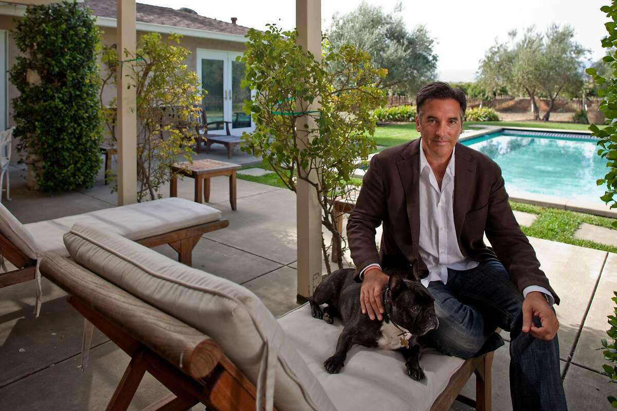 Michael Polenske, founder of Blackbird Winery with his dog Oliver pool side at his home in Napa, California on Oct. 9, 2009.