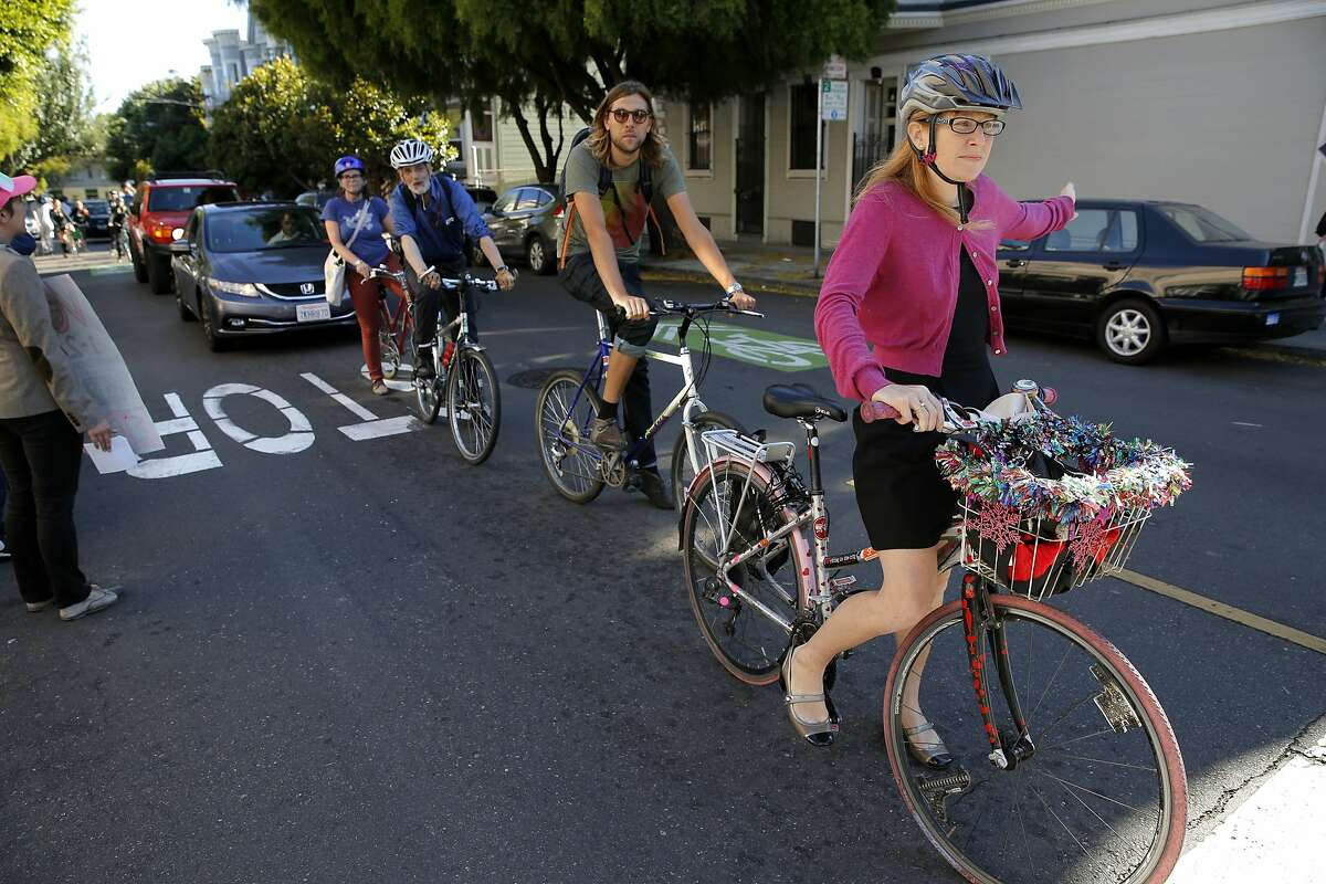 Sacha Ielmorini (right) executes a full stop at a stop sign during a biking protest on the way to a community meeting with SFPD Park Station Captain John Sanford in San Francisco, California, on Tuesday, Aug. 11, 2015.