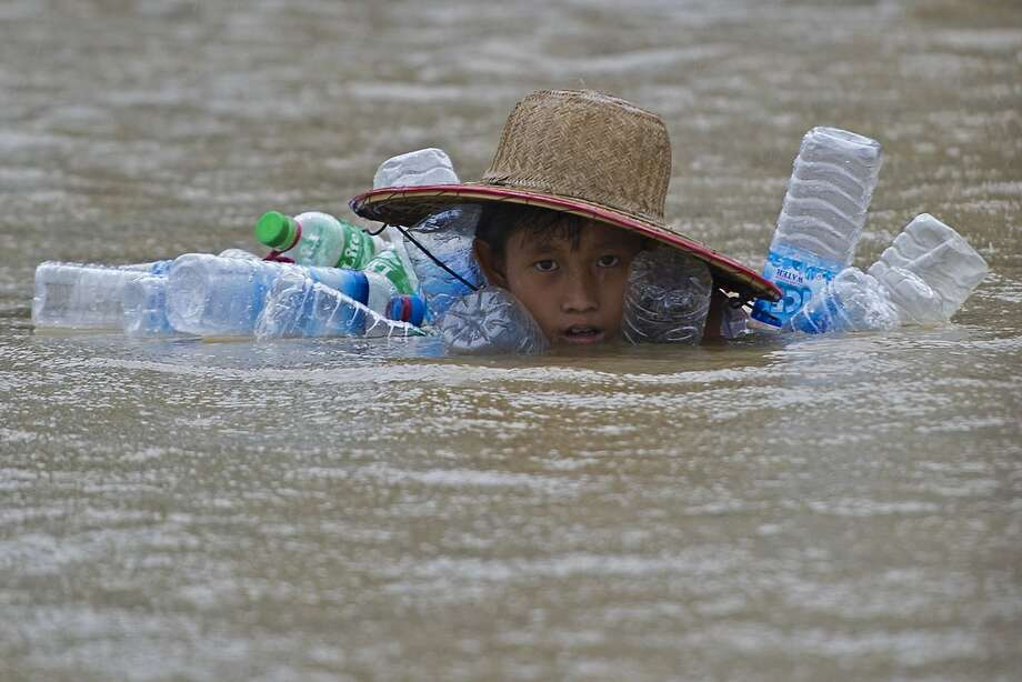 A flood-affected resident swims in floodwaters at Kyaut Ye village near the Hinthada town in Myanmar's Irrawaddy region on August 11, 2015.  Myanmar's president called for the evacuation of low-lying areas as the Irrawaddy river threatened to breach embankments, leaving villagers with just sand-bags to hold back churning waters that have hit much of the country. Photo: Ye Aung Thu, AFP / Getty Images