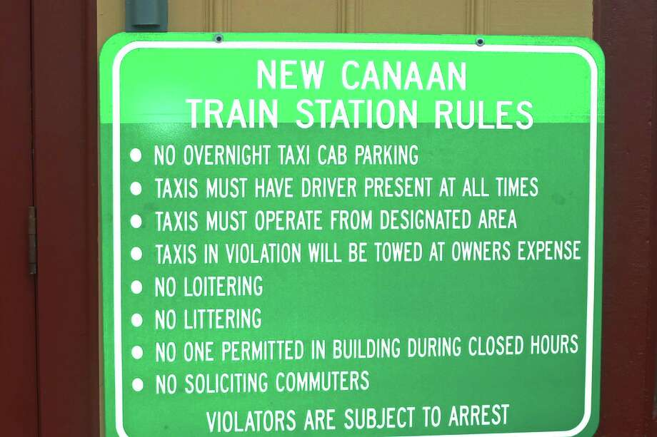 A new metal sign posted at the New Canaan train station has provoked the ire of cab drivers who feel they are unfairly targeted by new rules on their operations. Photo: Martin Cassidy / Hearst Connecticut Media / New Canaan News