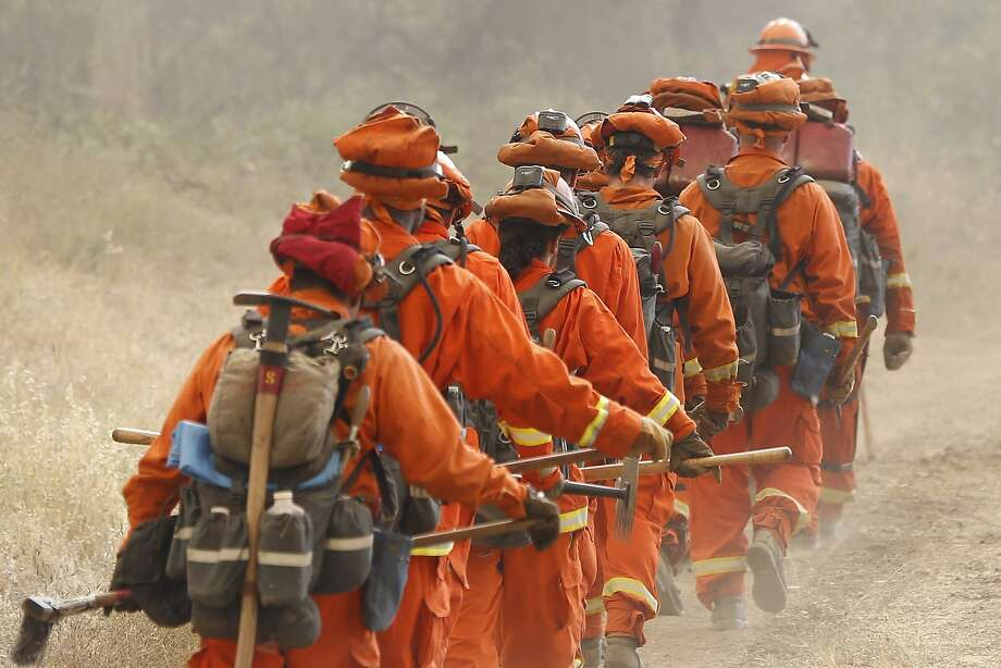 A group of inmate firefighters marches from their drop point on Morgan Valley Road to battle the Jerusalem Fire on August 11, 2015 near Lower Lake, California. The fire has consumed 16,000 acres after doubling in size overnight and is currently five percent contained.  Photo: Stephen Lam, Getty Images