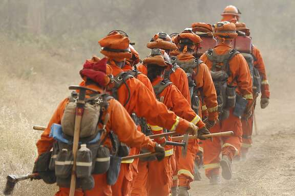 LOWER LAKE, CA - AUGUST 11:  A group of inmate firefighters marches from their drop point on Morgan Valley Road to battle the Jerusalem Fire on August 11, 2015 near Lower Lake, California. The fire has consumed 16,000 acres after doubling in size overnight and is currently five percent contained. (Photo by Stephen Lam/Getty Images)