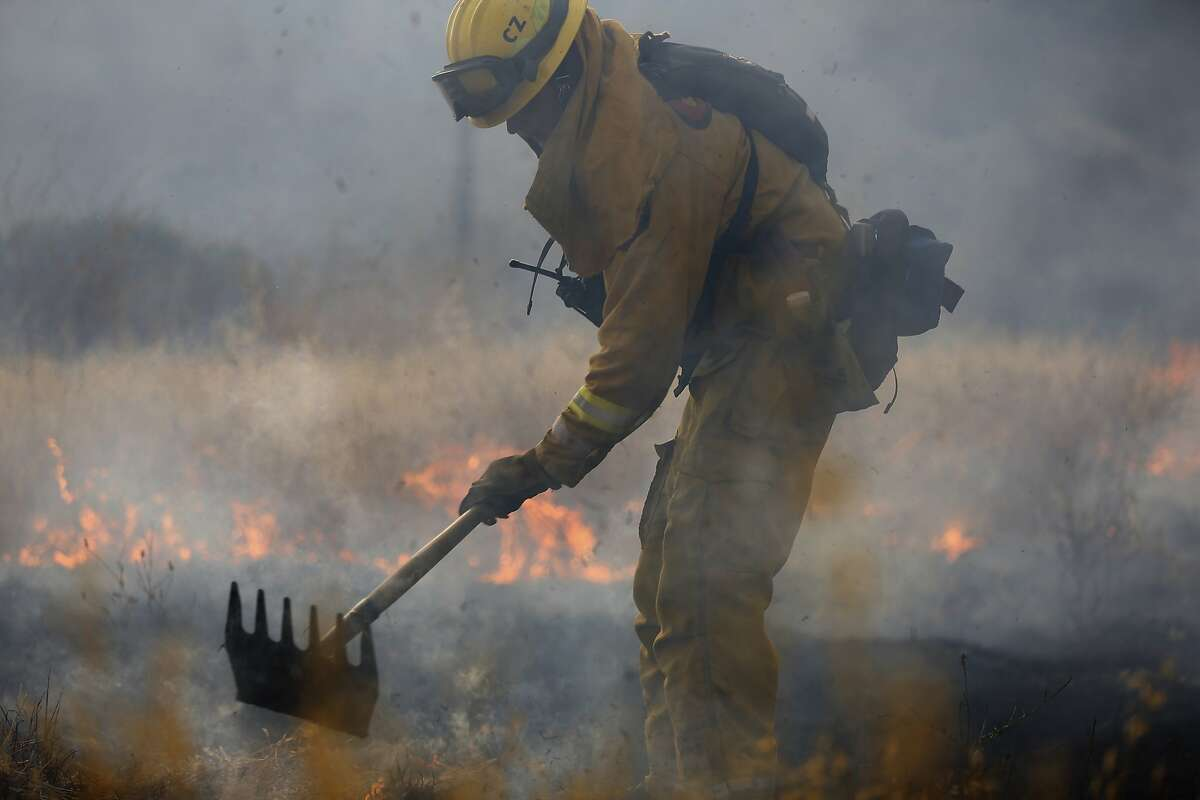 A Cal Fire firefighter uses a hand tool as he battles the Jerusalem Fire along Morgan Valley Road on August 11, 2015 near Lower Lake, California. The fire has consumed 16,000 acres after doubling in size overnight and is currently five percent contained.