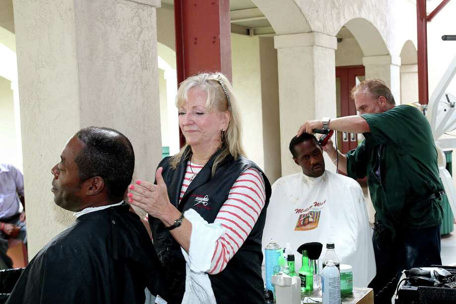 Carlos Kiser, from left, and Harold Monroe get their hair cut from  Barbara Goodson and David Taul at the Open Door Mission. Photo: Pin Lim, Freelance / Copyright Forest Photography, 2015.