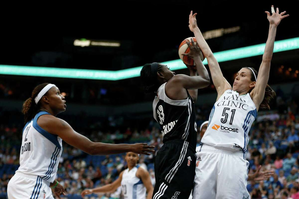 San Antonio Stars forward Sophia Young-Malcolm (33) tries to shoot against the defense of Minnesota Lynx guard Anna Cruz (51) during the first half of a WNBA basketball game, Tuesday, Aug. 11, 2015, in Minneapolis.