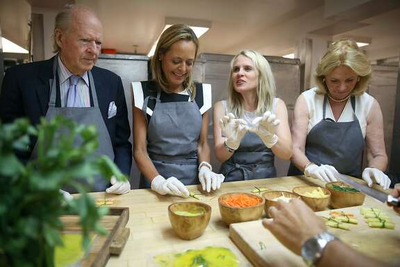 Austin Hills (left) and his wife Sara Hills (right) make appetizers with president of opera guild Charlotte Mayland (middle left) and opera ball co-chair Jane Mudge (middle right) at the McCalls catering kitchen in San Francisco, Calif.,  for the annual opera pre-gala menu tasting event on Tuesday, August 11, 2015.