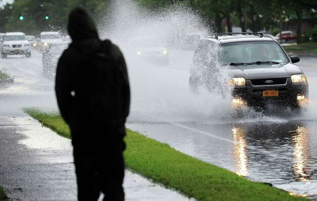A pedestrian struggles to stay clear of road spray along Wolf Road as heavy rains flood the roadway near Wolf Road Shoppers Park.  (John Carl D'Annibale / Times Union) Photo: John Carl D'Annibale, Albany Times Union