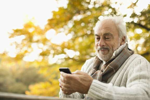 Older man using cell phone outdoors