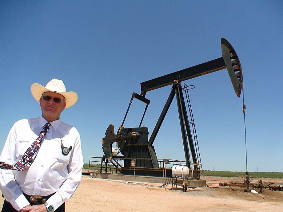 This June 24, 2008 photo shows Midland County, Texas Sheriff Gary Painter posing in front of an oil pump. The wide open oilfields of West Texas are ripe pickings for thieves these days. Some drive up to one of the thousands of pump jacks that dot the countryside and siphon crude out of the storage tanks. Some pull up to a drill site after the crews have gone for the night and haul away tools, pipes and equipment. Others take kickbacks, file false invoices or just plain steal knowing their bosses are too busy riding the oil boom to keep a close eye on accounting. (MIRA OBERMAN/AFP/Getty Images) Photo: MIRA OBERMAN, AFP/Getty Images