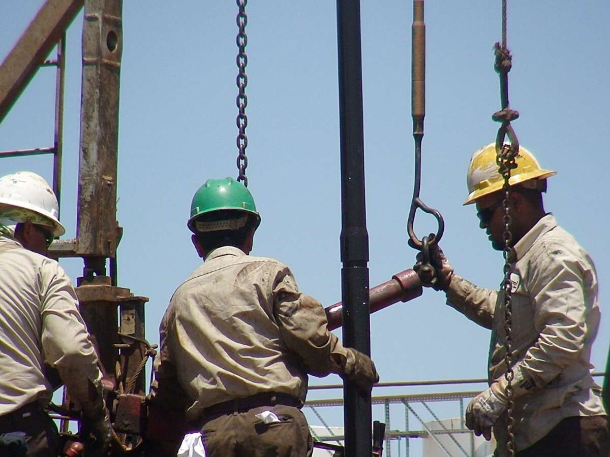 This June 24, 2008 photo shows oil workers on a rig in Midland County.