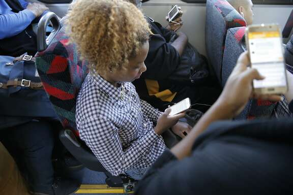 Monica Myers, (seated)  who is visiting from Philadelphia and Sarah Glover Johnson, (right) of Oakland, uses the A/C Transit Wi-Fi service on their smartphones aboard a bus from Oakland to San Francisco, Calif., on Wed. August 12, 2015.
