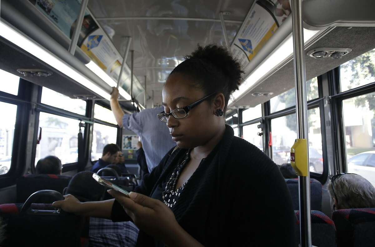 Sarah Glover Johnson, of Oakland, uses the A/C Transit Wi-Fi service on her smartphone aboard a bus from Oakland to San Francisco, Calif., on Wed. August 12, 2015.