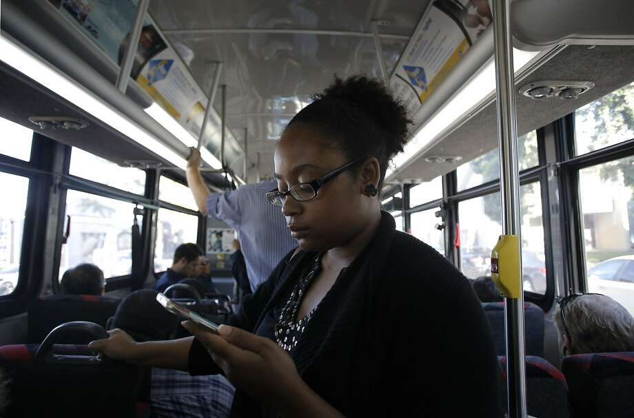Sarah Glover Johnson of Oakland uses AC Transit's free Wi-Fi service on her smartphone aboard a bus from Oakland to S.F. Photo: Michael Macor, The Chronicle