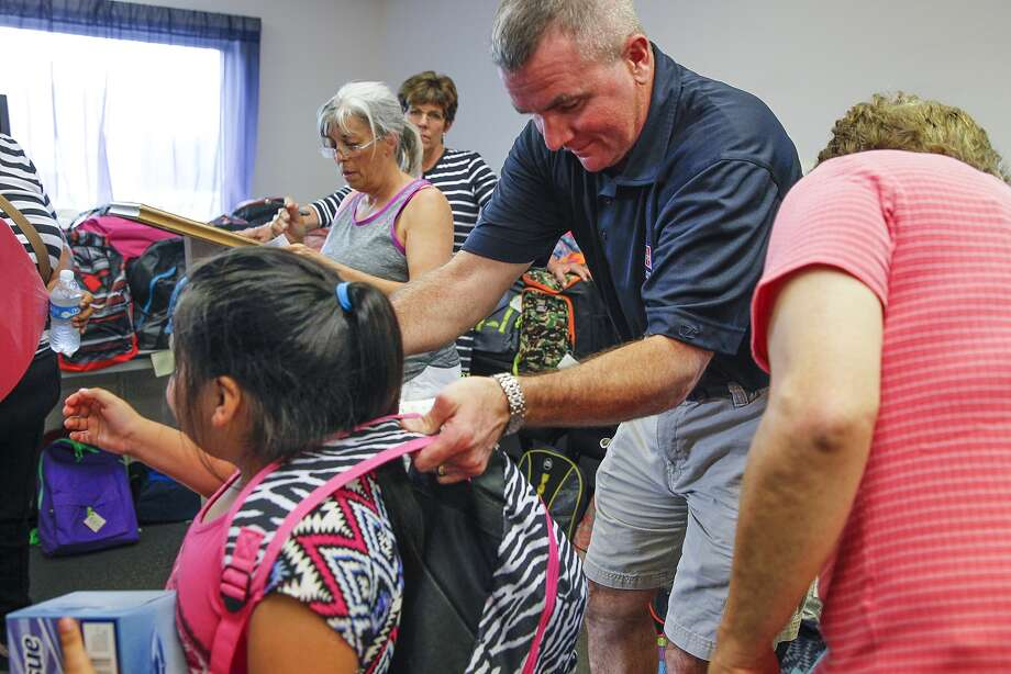 "Houston Northwest Community Center volunteer Charles Pryor helps Kelly Martinez with her new backpack  filled with school supplies. School backpacks were  distributed to 325 children during Houston Northwest Community Center's ""Stuff the Bus"" event on Aug. 11 at Bear Creek United Methodist Church. The community center serves Cy-Fair ISD and some Katy ISD elementary schools in 77084, 77095, 77041, and 77433 ZIP codes. Children also were able to choose three books to read from a wide assortment in the Houston Northwest Community Center's Books to Kids book program. Photo: Diana L. Porter, For The Chronicle / © Diana L. Porter"