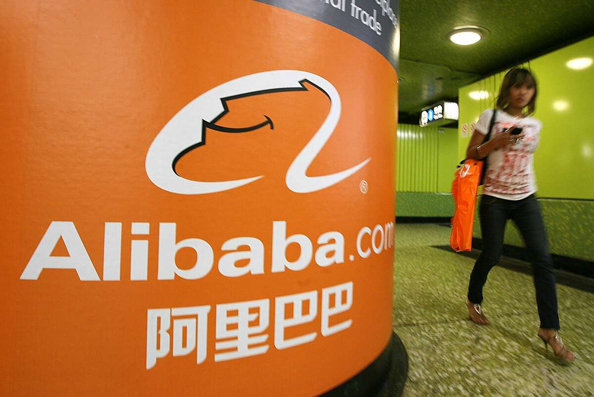(FILES) This file picture taken on October 29, 2007 shows a pedestrian walking past Alibaba.com advertising in Hong Kong. Chinese Internet giant Alibaba is to pay 4.6 billion USD for a near-20 percent stake in consumer electronics retailer Suning, the two companies said in a statement on August 10, 2015. AFP PHOTO / FILES / MIKE CLARKEMIKE CLARKE/AFP/Getty Images