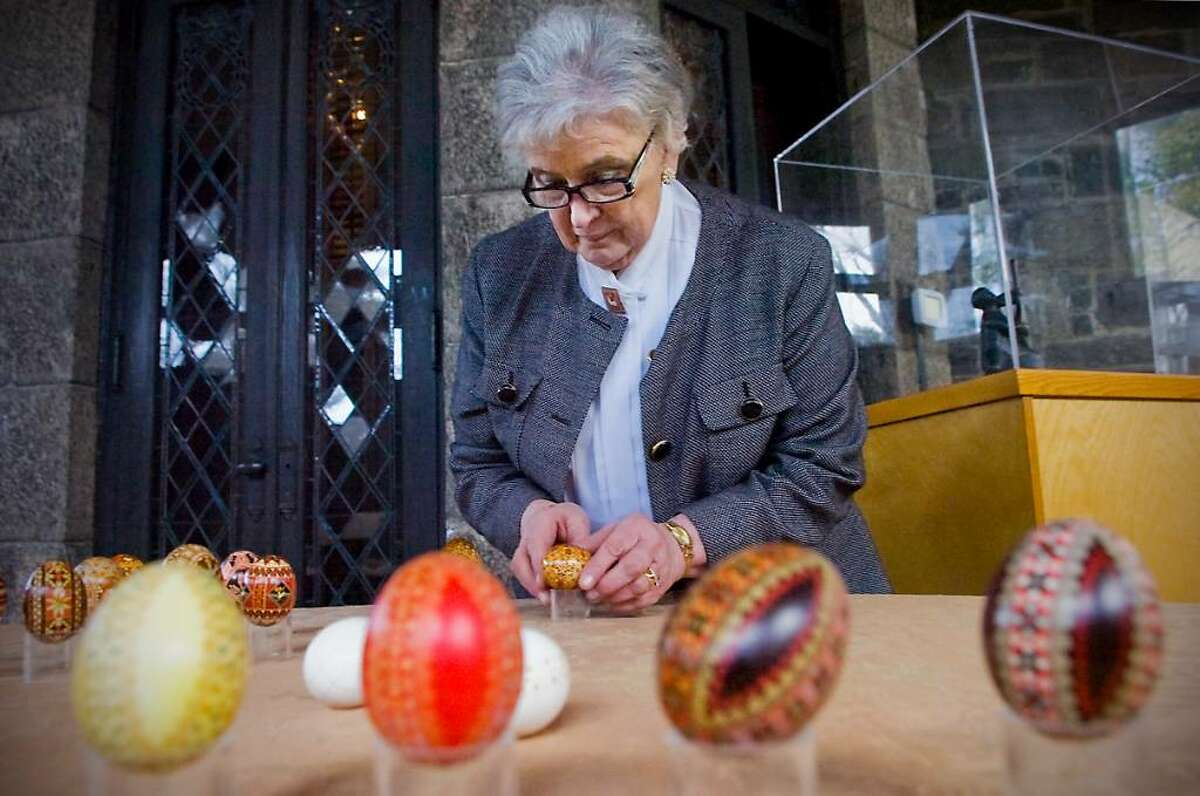 """Curator Lubow Wolynetz arranges some eggs in the """"Pysanka, The Ukrainian Easter Egg"""" exhibit at the Ukrainian Museum and Library of Stamford in Stamford, Conn. on Thursday, March 18, 2010. The traditional Ukrainian eggs are created with a variety of symbolic motifs."""