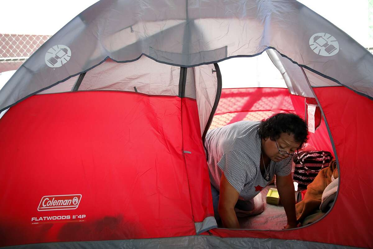 Olga, a homeless woman, cleans her tent in a homeless encampment at Division and Bryant streets beneath the highway overpass in San Francisco, California, on Wednesday, Aug. 12, 2015.