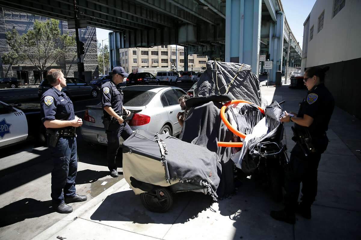 San Francisco Police Officers tell homeless man Nick Shaw to move his encampment from the sidewalk near Division and Bryant streets in San Francisco, California, on Wednesday, Aug. 12, 2015.