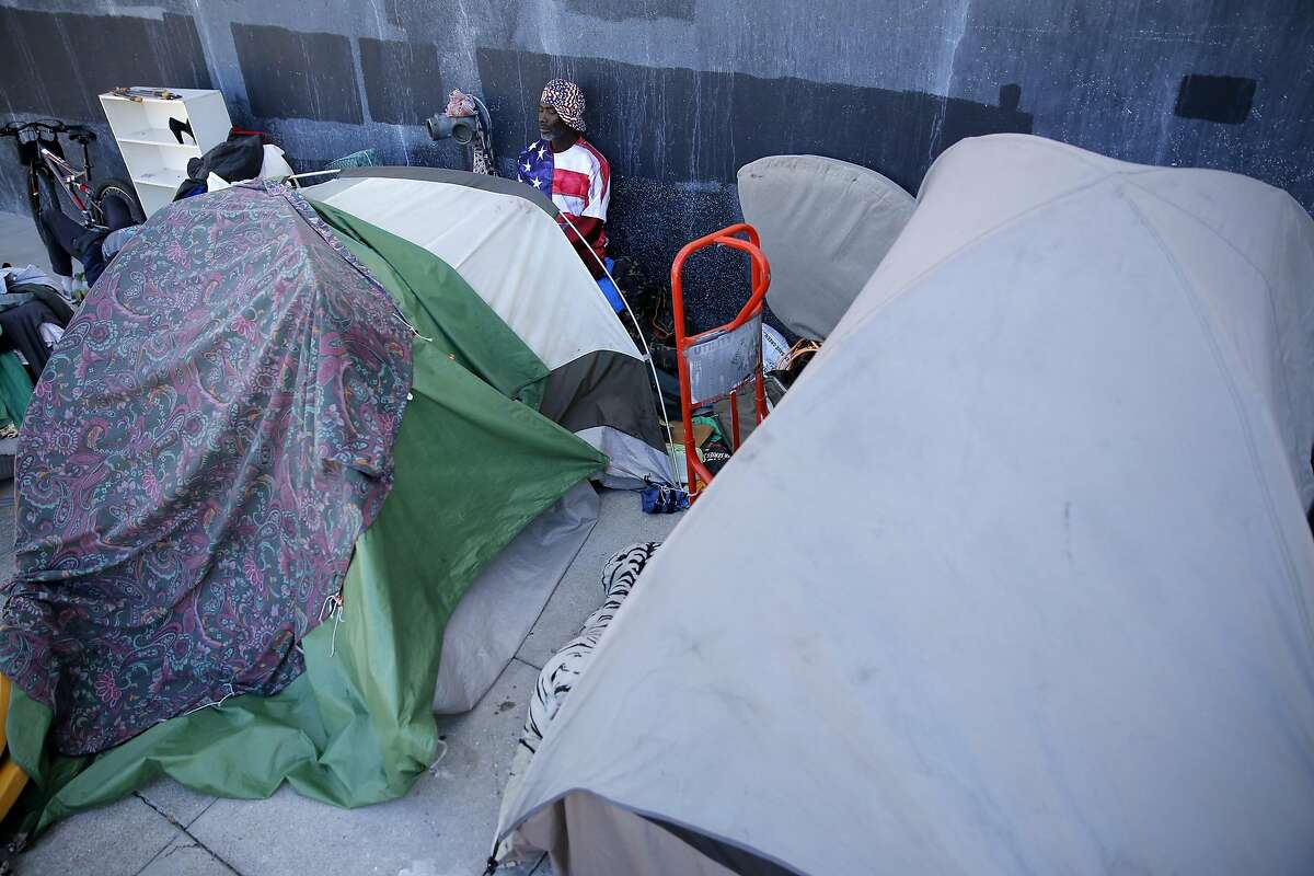 Steven, a homeless man, sits at his tent in a homeless encampment near Division and Bryant streets in San Francisco, California, on Wednesday, Aug. 12, 2015.