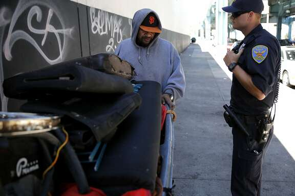 San Francisco Police Officer Suhrke tells Junior, a homeless man,  to move his encampment from the sidewalk near Division and Bryant streets in San Francisco, California, on Wednesday, Aug. 12, 2015.