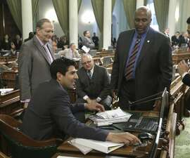Assembly members Bill Quirk, D-Hayward, left, Tom Lackey, R-Palmdale, seated in background, and Jim Cooper, D-Elk Grove, right, watch as Assemblyman Matthew  Dababneh, D-Encino, casts his vote for a measure  to end the use of secret grand jury proceedings to investigate police shootings,Thursday, July 16, 2015, in Sacramento,Calif.  The bill SB227 by Sen. Holly Mitchell, D-Los Angeles was approved on a 41-33 vote and sent to Gov. Jerry Brown for consideration. (AP Photo/Rich Pedroncelli)
