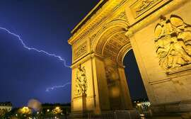 The dramatic Arc de Triomphe, built to honor Napoleon's victories, dominates Paris' skyline day and night.