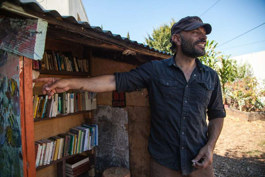 "Jaime Omar Yassin checks out the books at the ""people's library"" and community garden next to the abandoned Miller Avenue Library, Wednesday, Aug. 12, 2015, in Oakland, Calif. Photo: Santiago Mejia, Special To The Chronicle"