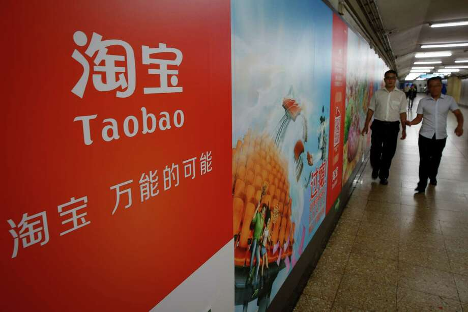 FILE - In this Sept. 18, 2014 file photo, people walk past an advertising billboard showing the mobile app of Alibaba's Taobao consumer-to-consumer site at a subway station in Beijing. Alibaba Group Holding Ltd. reports quarterly financial results before the market opens on Wednesday, Aug. 12, 2015. (AP Photo/Vincent Thian, File) ORG XMIT: NYBZ903 Photo: Vincent Thian / AP