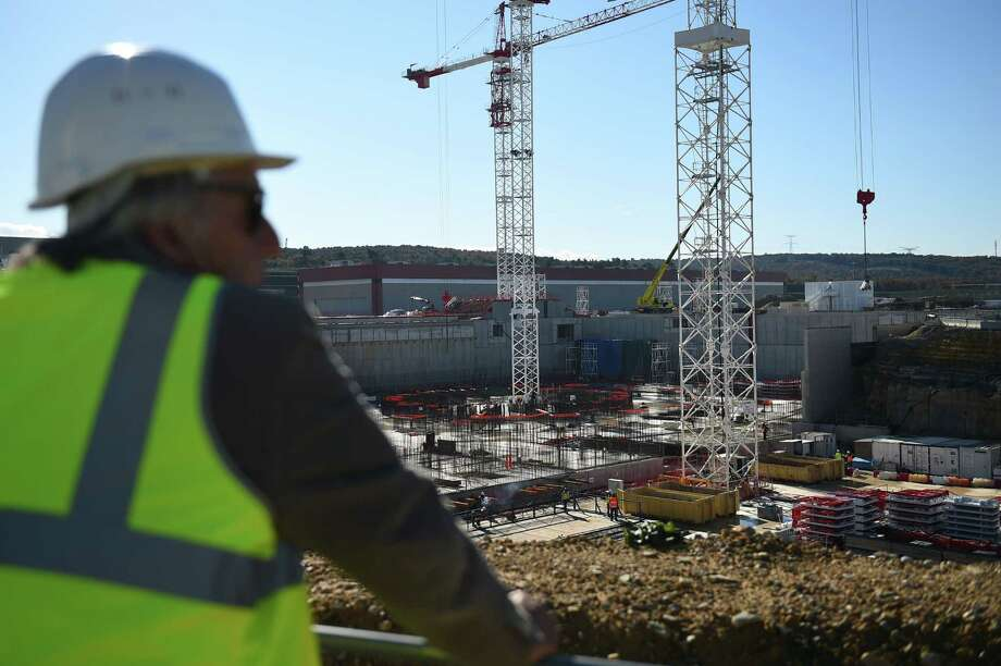 Technicians work at the construction site of the International Thermonuclear Experimental Reactor (ITER) on November 21, 2014 in Saint-Paul-les-Durance, southern France. The ITER nuclear fusion project, based at the French Atomic Energy Commission (CEA) research center of Cadarache in Saint-Paul-lez-Durance, was set up by the EU (which has a 45 percent share), China, India, South Korea, Japan, Russia and the US to research a clean and limitless alternative to dwindling fossil fuel reserves. AFP PHOTO / ANNE-CHRISTINE POUJOULATANNE-CHRISTINE POUJOULAT/AFP/Getty Images ORG XMIT: 4337 Photo: ANNE-CHRISTINE POUJOULAT / AFP