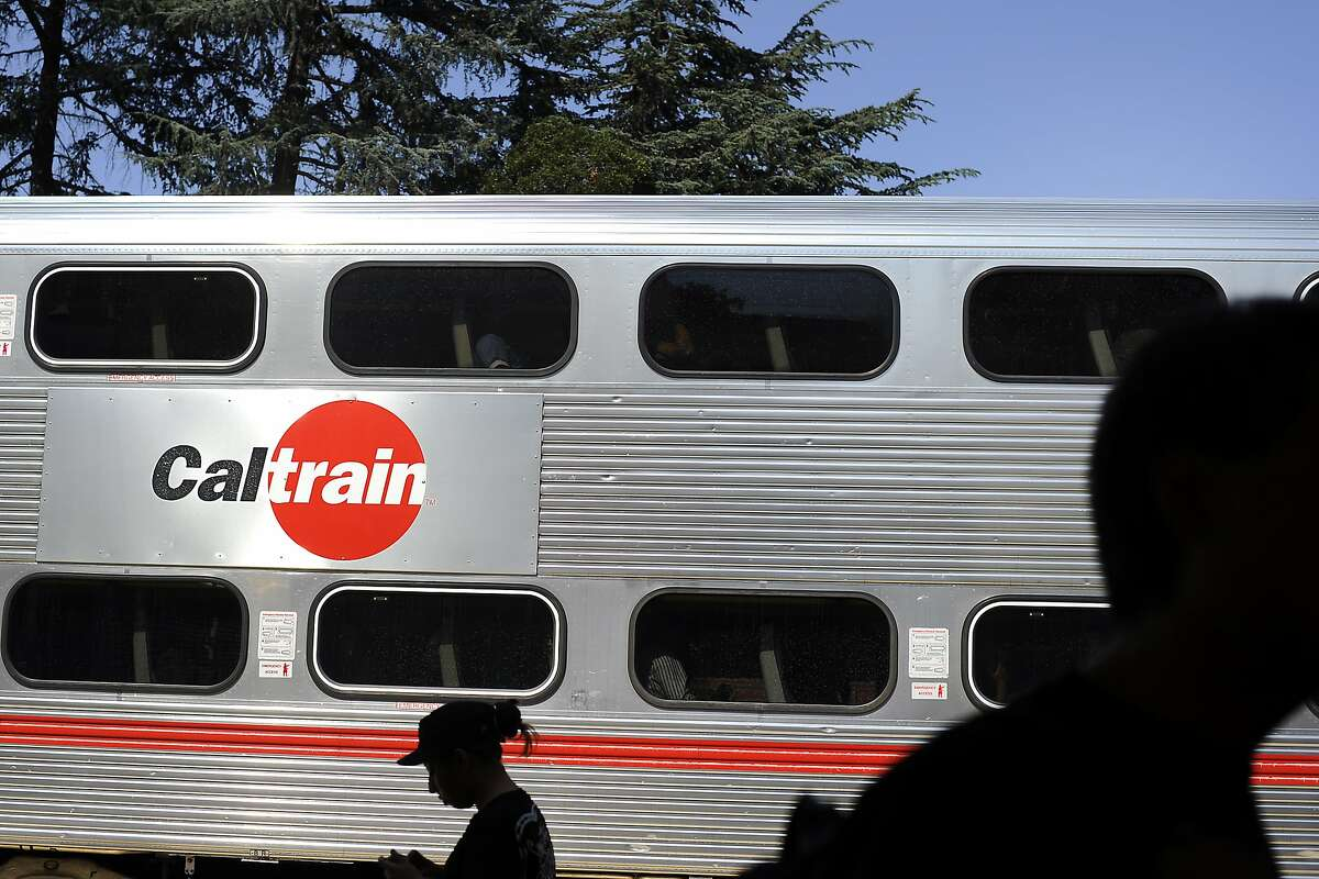 People wait on the platform as a Caltrain pulls into the University Ave. stop in Palo Alto, CA Friday, August 7, 2015.