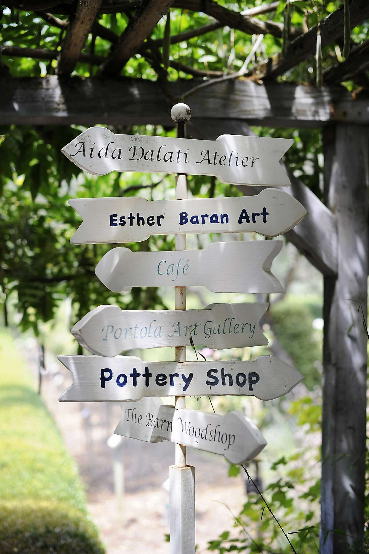 Signs point visitors to various artist's shops in the gardens of the Allied Arts Guild in Menlo Park, CA Monday, August 10, 2015.