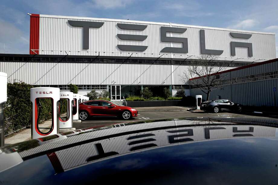 Tesla electric cars and charging stations are lined up outside the customer delivery center in front of Tesla Motors, California's only full-scale auto manufacturing plant, as seen on Thurs. Feb. 19, 2015,  in Fremont, Calif. Photo: Michael Macor, The Chronicle / ONLINE_YES