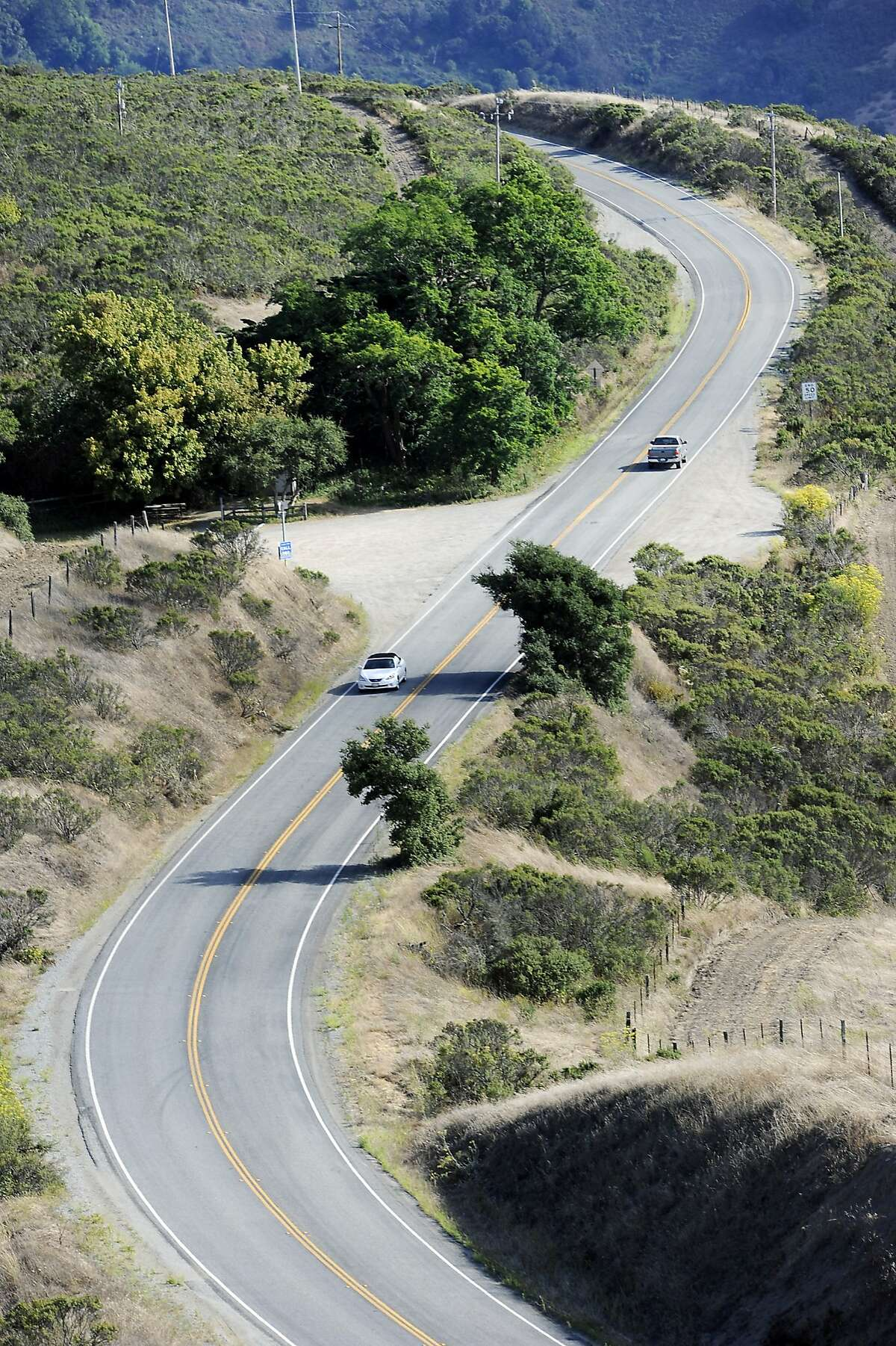 Cars pass along Sandhill Road as it winds past the Windy Hill Open Preserve in Portola Valley, CA Monday, August 10, 2015.