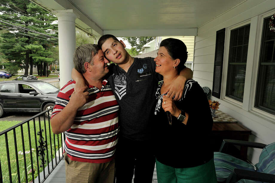 Terence Dervishi, center, poses with his mother, Keda Dervishi, and father, Dini Dervishi, at their home in Stamford, Conn., on Tuesday, Aug. 11, 2015. Terence has autism and despite his parents struggles to get him a proper special education program he has been without schooling for five years. The family is circulating a petition to force the Stamford Public Schools to give him a proper individualized education. Photo: Jason Rearick / Hearst Connecticut Media / Stamford Advocate