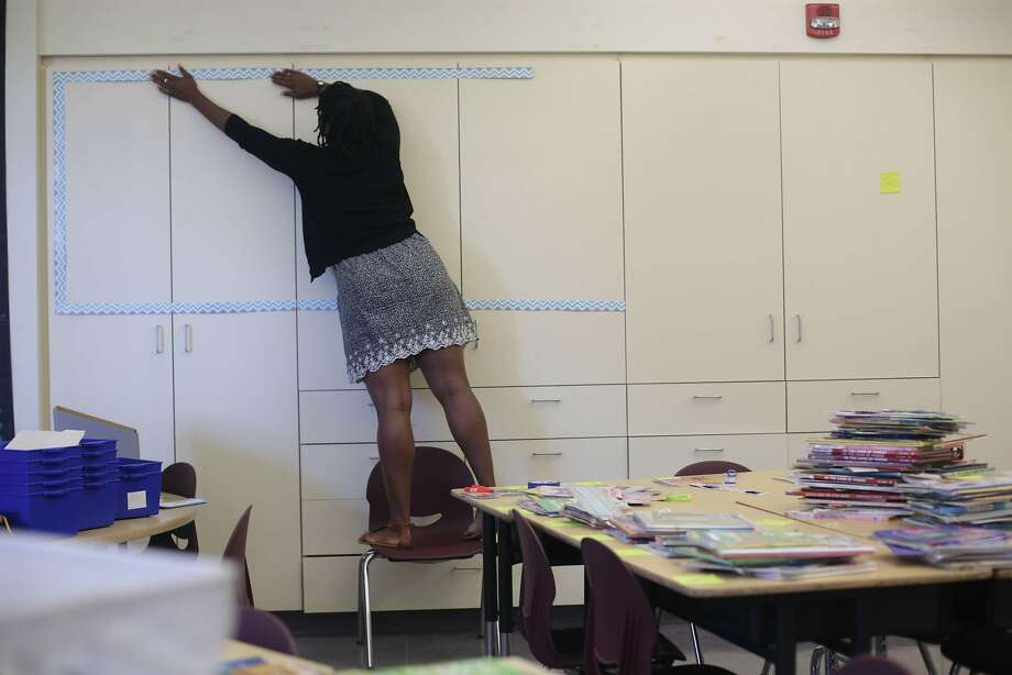 New teacher Ashli Duncan, above, sets up her classroom, top, at Bessie Carmichael Elementary School in San Francisco. She fears rent increases could force her to leave. Photo: Lea Suzuki, The Chronicle