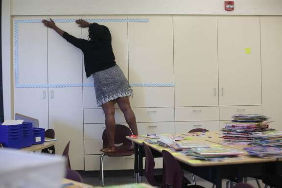 New SFUSD teacher Ashli Duncan sets up the border for her word board in her second grade classroom at Bessie Carmichael Elementary School on Wednesday, August 12, 2015 in San Francisco, Calif.