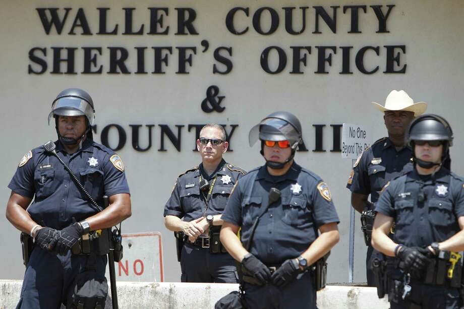 Law officials keep watch on a protest by the New Black Panther Huey P. Newton Gun Club for Sandra Bland and other black victims who have died at the hands of police outside the Waller County Sheriff's Office, Wednesday, Aug. 12, 2015, in Hempstead, Texas.  (Steve Gonzales /Houston Chronicle via AP) MANDATORY CREDIT Photo: Steve Gonzales, MBI / Associated Press / Houston Chronicle