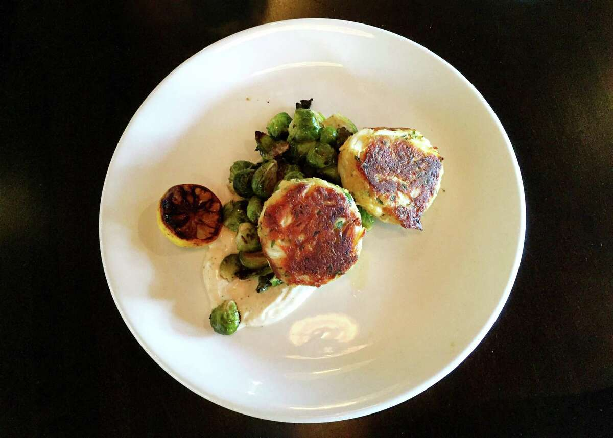 Crab cakes at The General Public are served with roasted Brussels sprouts, a charred lemon and garlic aioli.